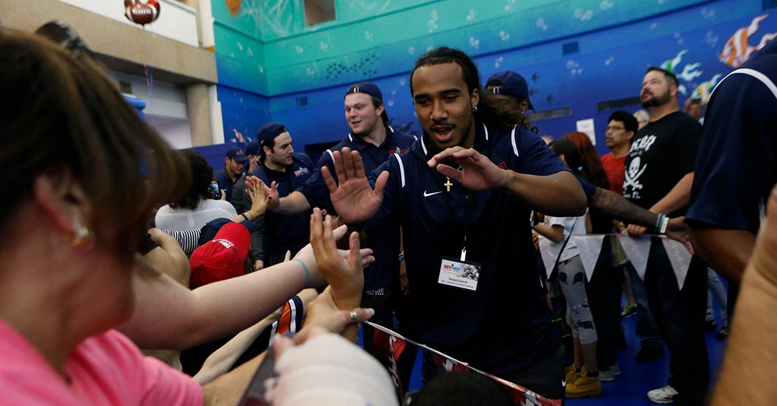 east west shrine game player high five with patients
